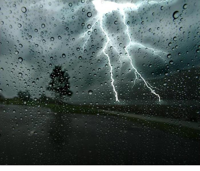 A large lighting strike just in front of person driving down road